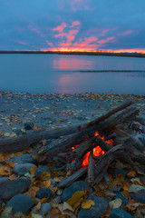 Lit campfire on the shore of Talkeetna river with red sunset