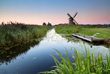 sunrise over river and Dutch windmill