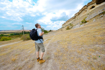 Adult man is hiking with his backpack