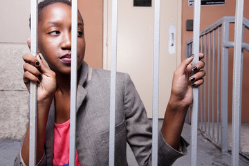 Woman posing behind bars