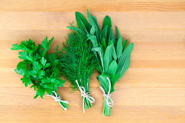 Fresh herbs: parsley dill and sage, over wooden background