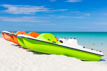 Colorful pedalos docked at a tropical beach