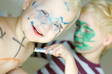 Children Coloring Their Faces with Markers