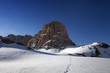 Snowy plateau and footpath against rock and blue sky in nice day