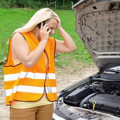 Frau in Warnweste hat Autopanne