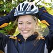Frau setzt Fahrradhelm auf