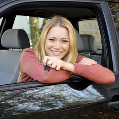 Frau in Auto hält Zünd-Schlüssel