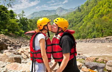Man and woman kissing for good lack before a rafting in Nepal.
