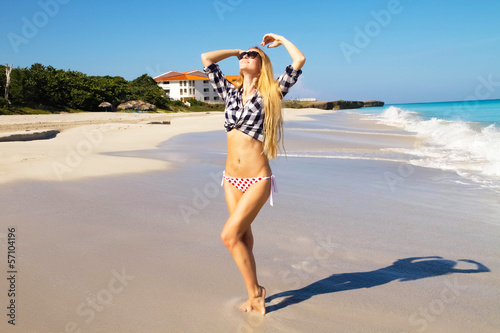 Portrait of young beautiful woman on the seashore sand