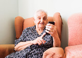 Old lady using a smartphone and looking at camera