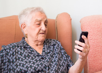 Elderly woman looking at a smartphone with confused expression