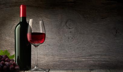Weinglas mit Flasche vor Holzwand