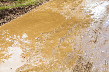 mud and puddle in rut of dirt ground road