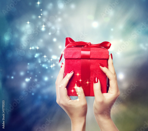 Red present box held up by in a woman's hands