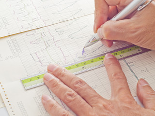 pen and ruler on hand examining scientific graph to analysis the