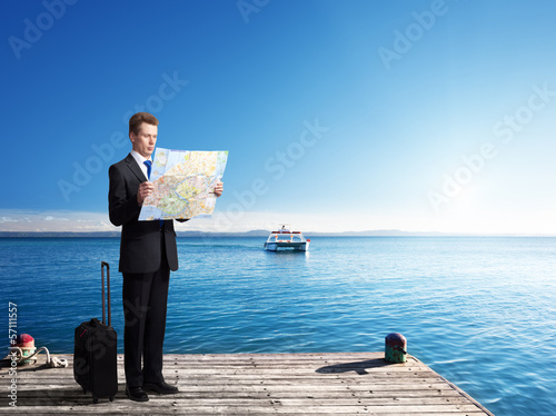 Business man standing on pier with map in hands