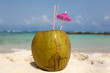 Coconut with drinking straw in the sand at the caribbean sea