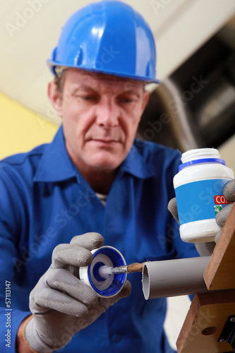 Plumber gluing grey plastic pipe