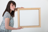 Brunette holding empty picture frame