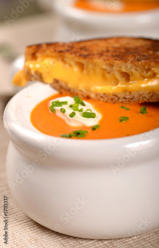 Delicious bowl of tomato soup with grilled cheese sandwich