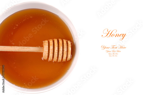 Closeup of a bowl of amber honey with a honey wand isolated on w