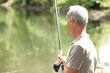elderly man fishing by river