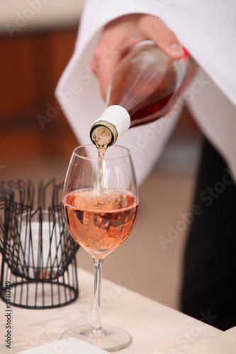 Waiter's hand pouring a bottle of rose wine