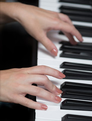 A hand of a girl playing piano. Selective focus.