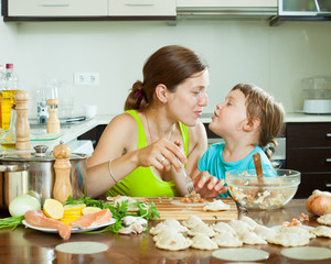 woman with girl cooking fish dumplings together  at home kitchen