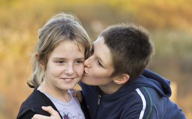 A boy kissing a little girl on the cheek