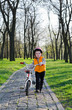 Little boy pushing his bicycle in a park