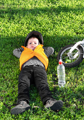 Small boy taking a rest on the grass