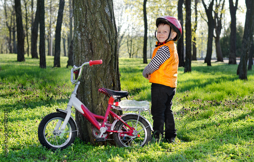 Little boy standing grinning alongside his bicycle