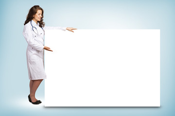 young woman doctor standing near a blank banner