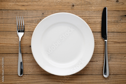 Plate, fork and knife on wooden background - 57121393