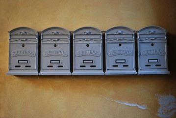 Row of gray mailboxes in vintage style on old yellow wall