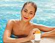 Girl putting sun block near pool holding white sun tan lotion b