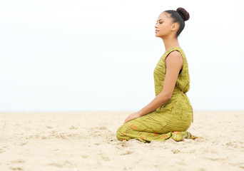 Young woman sitting alone and meditating at the beach