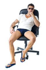 Attractive young man in t-shirt, with naked legs on office chair