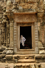 Buddhist nun covers her head in a temple in angkor