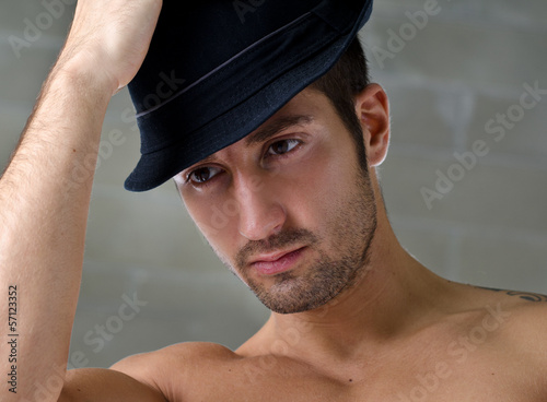 Headshot of handsome young man wearing hat
