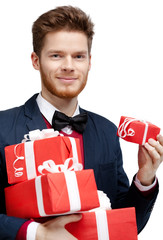 Man with bow tie carries a lot of different sized presents
