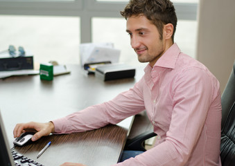 Handsome, happy office worker smiling while using computer