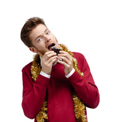 Man eats small cake with candle in it, isolated on white