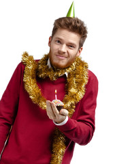Smiley man with tinsel holds small tart, isolated on white