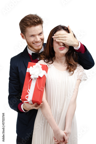 Giving a present man covers eyes of his pretty girlfriend