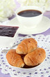 Tasty croissants and cup of coffee on table close-up