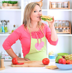 Happy smiling woman in kitchen preparing  sandwich