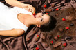 Woman lying on brown atlas covered by chocolate and candies