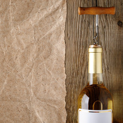 Wine bottle with corkscrew on wood